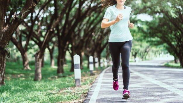 mulher-asiatica-nova-que-corre-na-estrada-na-natureza_42682-410